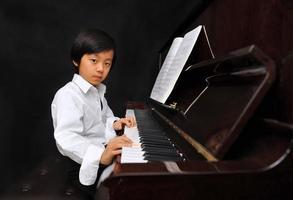 jonge Aziatische jongen piano spelen