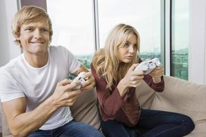 jong koppel spelen van video game in de woonkamer foto