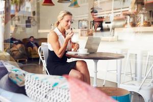zakenvrouw zitten aan een tafel in de kleine koffieshop foto