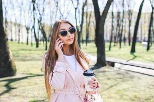 modieuze vrouw met telefoon en koffie in de stad. mode vrouw in een zonnebril en roze jas buiten foto