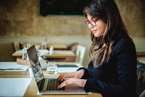 gelukkig meisje te typen op de computer in het restaurant foto