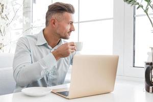 knappe zakenman die met laptop werkt en kop koffie in koffie heeft foto