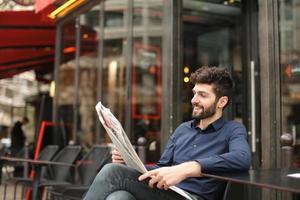 welvarende zakenman bericht aan het typen door smartphone in café met foto