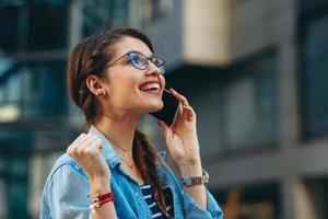 jonge vrouw ontvangt goed nieuws via de telefoon in de stad foto