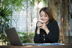 jonge mooie zakenvrouw genieten van koffie tijdens het werk op draagbare laptopcomputer. foto