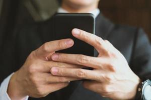 smartphone van de zakenmanholding & gebruikend app. man sms-bericht buitenshuis. sociale netwerkcommunicatie, draadloze verbinding, levensstijlconcept