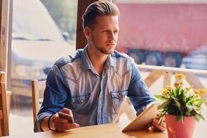een man met een tablet-pc en smartphone in café. foto