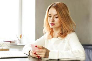 aantrekkelijke hipster jonge vrouw in moderne loft cafe coffeeshop restaurant. schrijver, blogger, ontwerper, freelancer, werkproces op afstand. e-shoppen, online shoppen, m-shoppen. foto