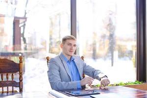 interieurontwerper zit in café, met behulp van slimme horloge in de buurt van roll p foto
