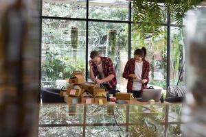 kleine ondernemer opstarten op de werkplek. freelance man & vrouw verkoper check productbestelling voor levering. online verkoop, e-commerce, verzendconcept foto