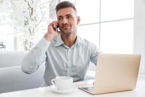 knappe zakenman die met laptop werkt en telefonisch in koffie spreekt foto