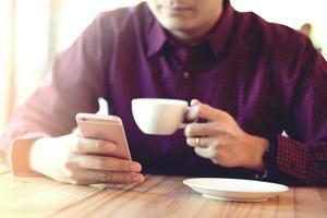 knappe zakenman in een telefoon gebruiken in de coffeeshop. foto