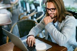 man aan het werk op laptop vanuit café buitenshuis