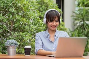 Aziatische jonge vrouw ontspannen door muziek met laptop te luisteren foto