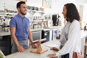 vrouwelijke klant bestellen aan de balie in een coffeeshop foto