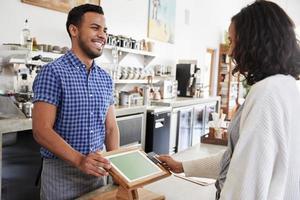 vrouw die contactloze kaartbetaling verricht bij een koffiewinkel foto
