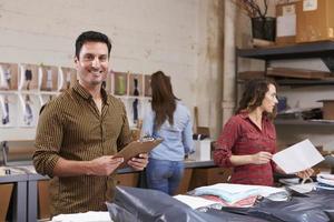 Spaanse man pakt bestellingen voor distributie in, glimlacht naar camera foto