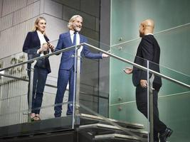 mensen uit het bedrijfsleven verwelkomen bezoeker op trappen foto