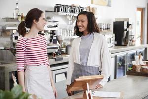 twee vrouwelijke coffeeshop eigenaren kijken naar elkaar foto