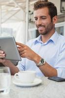 vrolijke jonge zakenman die op tablet werkt foto