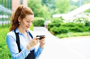 vrolijk, meisje opgewonden door wat ze op een mobiele telefoon ziet foto