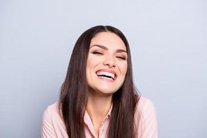 portret van vrij trendy charmante vrolijke grappige vrouw in klassieke overhemd lachen met brede gezonde witte stralende glimlach geïsoleerd op grijze achtergrond camera kijken foto