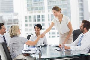 leidinggevenden handen schudden tijdens een zakelijke bijeenkomst foto