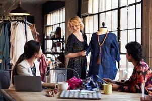 drie modeontwerpers in vergadering bespreken kledingstuk foto