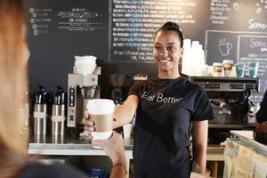 vrouwelijke barista klant met afhaalmaaltijden koffie in café foto