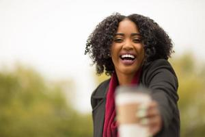vrouw overhandigt u een kopje koffie. foto