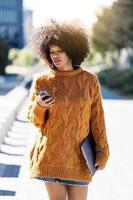 portret van aantrekkelijke afro vrouw met behulp van mobiele telefoon in de straat