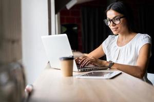 op zoek naar nieuwe oplossing. nadenkend jonge mooie zakenvrouw in glazen die op laptop werkt zittend op haar werkplek foto