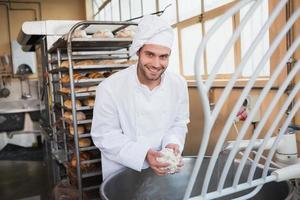 glimlachende bakker die deeg in industriële mixer voorbereidt foto
