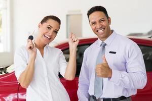 vrouw heeft zojuist een nieuwe auto gekocht bij de dealer