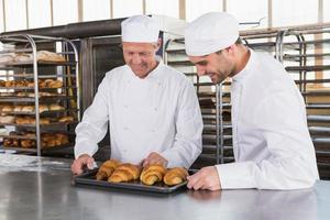 lachende bakkers op zoek naar dienbladen met croissants foto