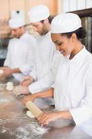 team van bakkers werken aan balie