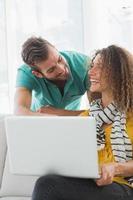 glimlachende vrouw op de bank die haar collega haar laptop toont foto