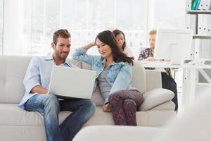 lachende jonge ontwerpers die op laptop op de Bank werkt foto