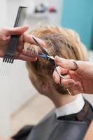 kapper die het haar van klanten snijdt foto