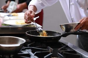 chef-kok in de keuken van het restaurant koken foto
