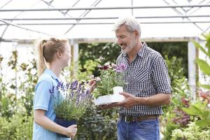 mannelijke klant vraagt personeel om plantenadvies bij tuincentrum