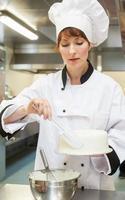 behoorlijk gefocuste chef-kok die een cake afmaakt met glazuur foto
