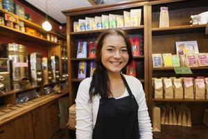 portret van vrouwelijke verkoper glimlachend in coffeeshop foto
