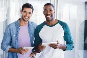 portret van glimlachende mannelijke collega's met behulp van digitale tablets foto