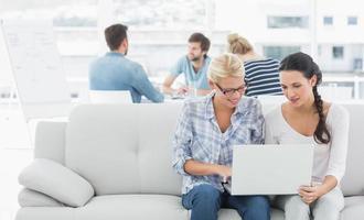 vrouwen die laptop met collega's op achtergrond met behulp van op creatief kantoor foto