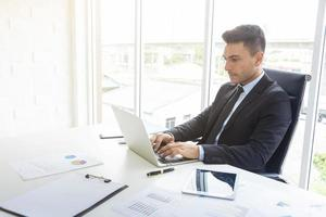 knappe zakenman werken bij een bureau met laptop en papier grafiek in kantoor. professioneel zakenman en technologieconcept. foto