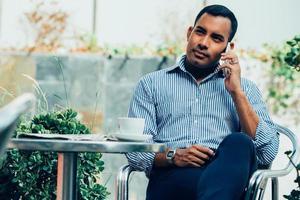 ontspannen Spaanse man praten over telefoon in café foto