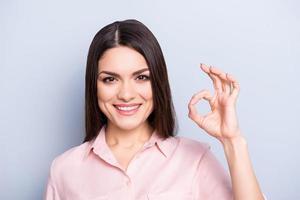 Portret van mooie, charmante, trendy, leuke, aardige vrouw met stralende glimlach in klassiek overhemd dat ok teken toont met vingers die camera bekijken die op grijze achtergrond wordt geïsoleerd foto