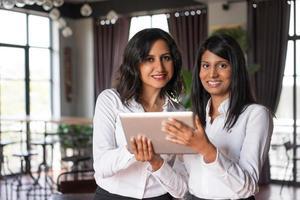 twee lachende vrouwelijke collega's met behulp van tablet-computer in café foto