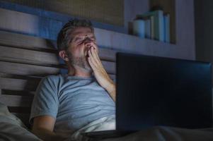 aantrekkelijk moe en beklemtoonde workaholic mens die laat op de avond uitgeput aan bed bezig met laptop computer geeuwen slaperig gevoel en overwerkt in zaken project deadline spanning concept foto
